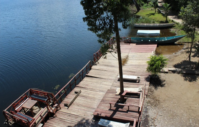 The deck of the boat jetty surrounded by trees.
