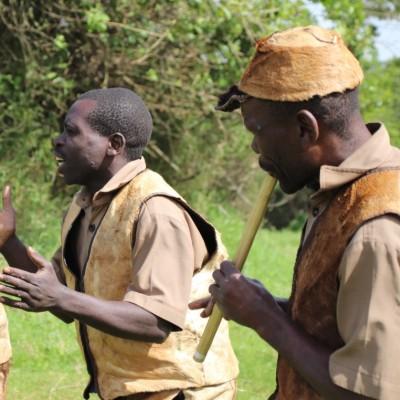 Three Batwa men play instruments and dance.